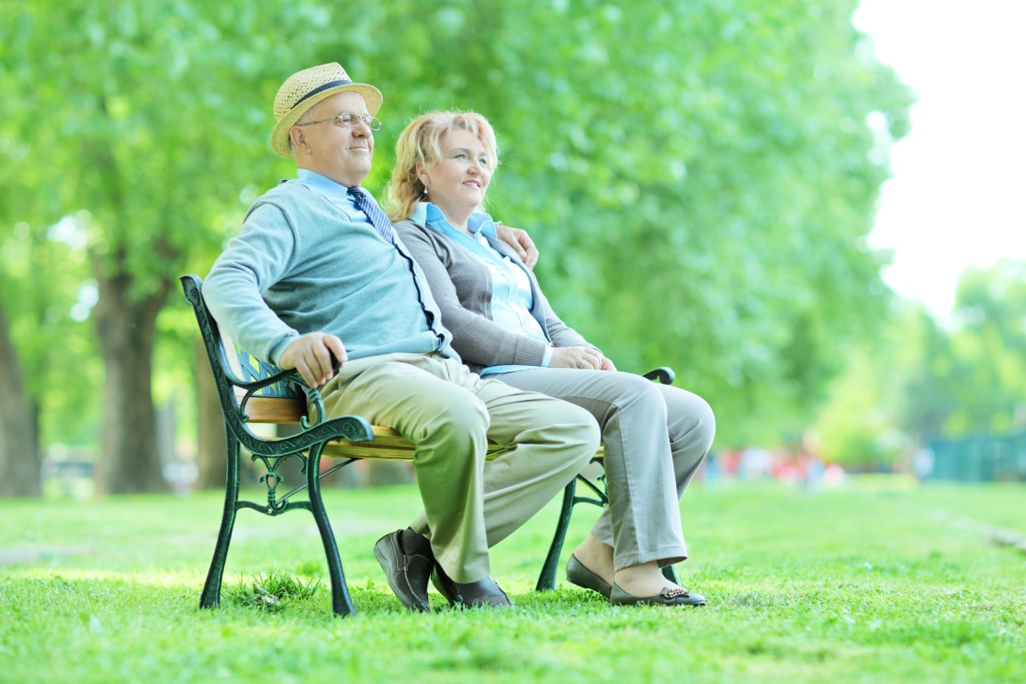Elderly couple relaxing on a bench in park